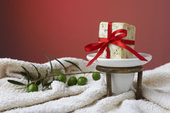 Handmade olive soap with olive branch and a towel, as a gift. Royalty Free Stock Photo