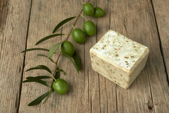 Handmade olive soap with olive branch on wooden table. Royalty Free Stock Image
