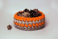 Handmade  orange basket with pine cones. Crochet round orange basket with pine cones Stock Photography