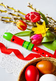 Handmade painted eggs with daffodils, tulip and pussycats flower and wooden music instrument flute. Stock Photos