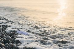 Paper boat lies on the seafront at sunrise. Handmade paper boat lies on the seafront at sunrise stock image