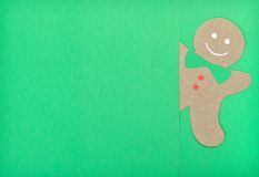 Gingerbread man. Handmade of paper cut out gingerbread man under green background in horizontal stock illustration