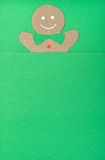 Gingerbread man. Handmade of paper cut out gingerbread man under green background in vertical Royalty Free Stock Image