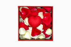 a handmade paper heart and rose petals in a paper box stock images
