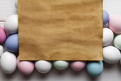 Handmade paper sheet and colorful eggs on white background Royalty Free Stock Photos