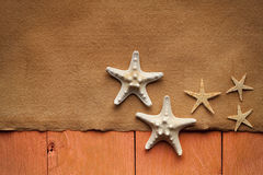 Handmade paper sheet and starfish on wooden planks Royalty Free Stock Photos