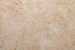 Handmade paper texture with vegetable fibers like straw. In delicate tones, yellows, oranges, browns and vanilla royalty free stock photo