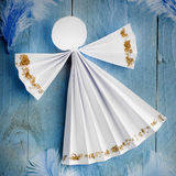 Handmade paper white angel on blue feather background. Royalty Free Stock Image