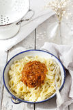 Handmade pasta with ragout sauce on plate on vintage white table with colander Royalty Free Stock Photos