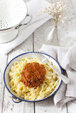 Handmade pasta with ragout sauce on plate on vintage white table with colander Royalty Free Stock Images