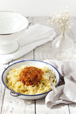 Handmade pasta with ragout sauce on plate on vintage white table with colander Royalty Free Stock Photo