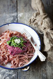 Handmade pasta tagliatelle with beetroot pesto, rocket and parmesan Stock Photo