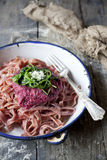 Handmade pasta tagliatelle with beetroot pesto, rocket and parmesan on plate Stock Photography
