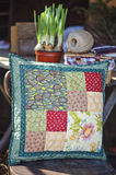 Handmade patchwork cushion with narcissus bulbs on background. In spring garden Royalty Free Stock Photos