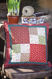 Handmade patchwork cushion with narcissus bulbs on background Stock Photos