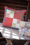 Handmade patchwork cushion with sewing tools on wooden table Stock Photo