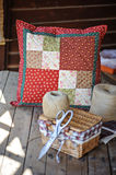 Handmade patchwork cushion with sewing tools on wooden table Royalty Free Stock Image