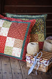 Handmade patchwork cushions with sewing tools on wooden table Stock Photography