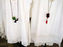 Handmade Pendants. Handmade craft pendants displayed on white lacy women's shirts or blouses, outside tourist craft shop, Tinos, Greek Island, Greece Royalty Free Stock Image