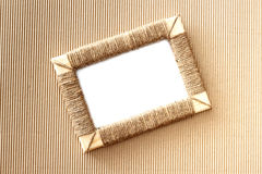 Handmade photo frame braided jute against corrugated fibreboard background Royalty Free Stock Photos