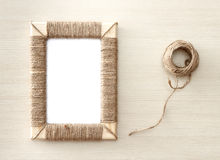Handmade photo frame braided jute against wooden background Stock Photos