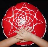 Handmade pillow. Jung girls hands on the handmade pillow Royalty Free Stock Images
