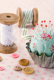 Handmade pincushion on floral fabric background Royalty Free Stock Photos