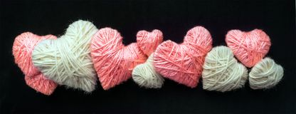 Handmade pink and white wool yarn heart  on black banner. Many pink and white hearts of knitting threads background with copyspace. Hobby, love and romance Royalty Free Stock Images