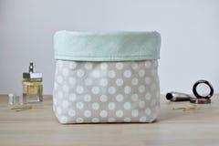 Handmade polka dot fabric bin on the wooden table. Handmade polka dot cosmetic organizer fabric bin on the wooden table stock image