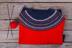 Handmade pullover and knitting supplies. Metal needles and ball of red wool yarn. Warm wear for cold winter days Stock Photo