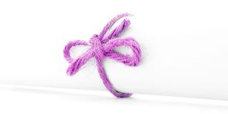 Handmade różowy linowy łęk wiążący na białej wiadomości rolce odizolowywającej Fotografia Stock