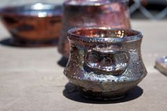 Handmade raku pottery cup straight out of the kiln Stock Photo