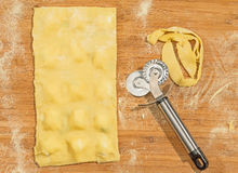 Handmade  ravioli dough,covered with flour and wheel dough cutter placed on wooden table. Stock Photo