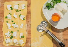 Handmade  ravioli dough  with fresh egg,cheese,parsley and wheel dough cutter placed on wooden table. Stock Photography