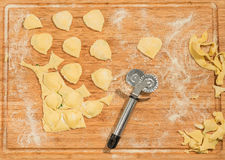 Handmade ravioli and raw dough covered with flour.Wheel dough cutter placed on wooden table. Royalty Free Stock Image