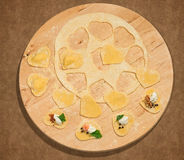 Handmade ravioli in the shape of heart,open and closed, placed on a round centerpiece of wood. Royalty Free Stock Image
