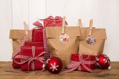 Handmade red christmas presents and bags. Handmade christmas presents wrapped in paper bags and presents with red white checked ribbon on wooden white Royalty Free Stock Image