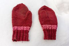 Handmade red mittens on white snow royalty free stock photography