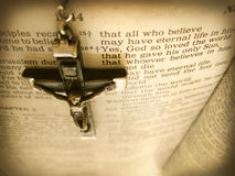 Handmade Rosary Crucific Hangs over Bible Verse from Heaven's View. This sepia toned photograph of an antique Italian handmade cross hanging over the Bible verse Stock Image
