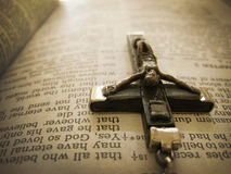 Handmade Rosary Crucific Hangs over Bible Verse from Heaven's View. This sepia toned photograph of an antique Italian handmade cross hanging over the Bible verse Stock Photos