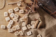Handmade scandinavian wooden runes on a wooden vintage background. Concept of fortune telling and prediction of the stock image
