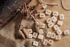 Handmade scandinavian wooden runes on a wooden vintage background. Concept of fortune telling and prediction of the stock photo