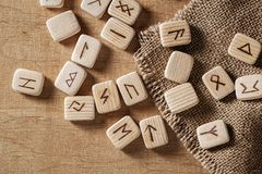 Handmade scandinavian wooden runes on a wooden vintage background. Concept of fortune telling and prediction of the stock images