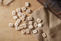 Handmade scandinavian wooden runes on a wooden vintage background. Concept of fortune telling and prediction of the.  royalty free stock image