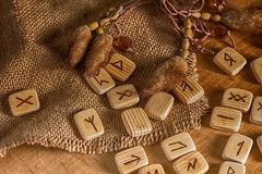 Handmade scandinavian wooden runes on a wooden vintage background. Concept of fortune telling and prediction of the stock photos