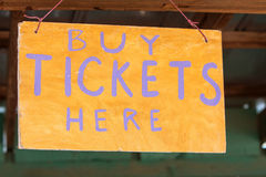 Handmade Sign Instructs Carnival Patrons Where To Buy Tickets. Handmade sign reads Buy Tickets Here at grassroots carnival Royalty Free Stock Image