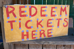 Handmade Sign Instructs Carnival Patrons Where To Redeem Tickets. Handmade sign reading Redeem Tickets Here sits at booth of carnival Royalty Free Stock Photos
