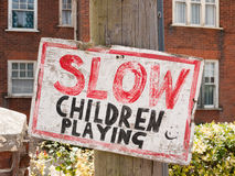 Handmade sign for slowing down near children transport. Handmade unique red, black and white slow children playing sign on post outside Royalty Free Stock Images