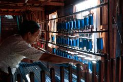 Handmade silk fabrication from Lotus in Inle Lake, Myanmar, Burma. Burmese worker make silk from lotus in traditional wooden weaving and handworking factory in stock photography