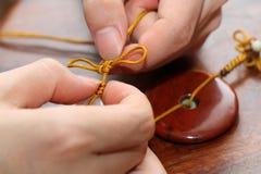 Handmade silk weaving. Woven handicrafts hand close-up Royalty Free Stock Photography